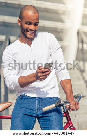 Handsome young Afro American man in casual wear is using smartphone and smiling while leaning on his bike, standing outdoors