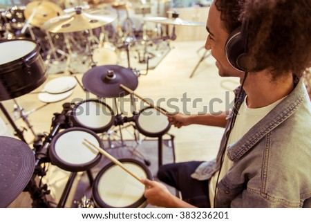 Handsome young Afro-American man in jeans jacket smiling while playing electronic drums in a musical shop - stock photo