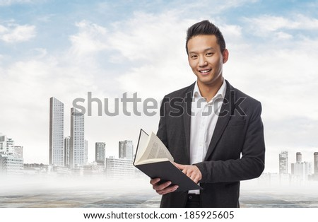 handsome young asian business man holding a book - stock photo