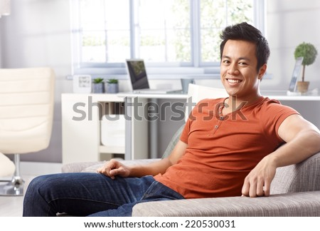 Handsome young Asian man sitting at home on sofa, smiling happy, looking at camera. - stock photo