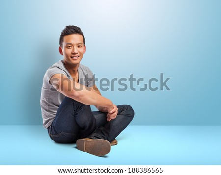 handsome young asian man sitting on a blue room - stock photo