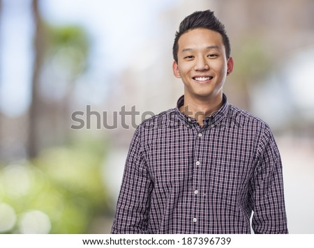 Handsome young asian man smiling wearing a plaid shirt - stock photo