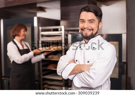 Handsome young baker is standing and crossing his hands. The man is smiling and looking forward positively. His female assistant is working with pastry happily - stock photo