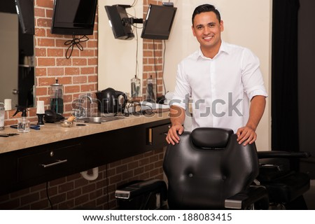 Handsome young barber standing behind a barber chair and greeting clients with a smile - stock photo