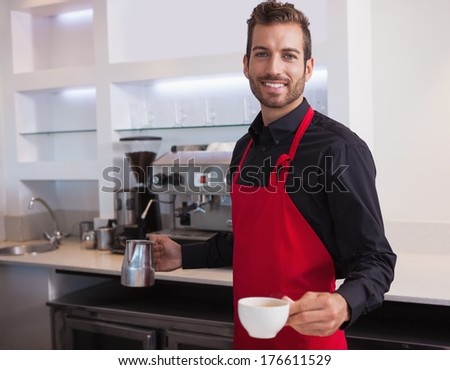 Handsome young barista holding jug and cup of coffee in a cafe
