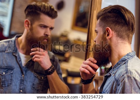 Handsome young bearded barber  looking in the mirror and adjusting his beard while standing in the barber shop - stock photo