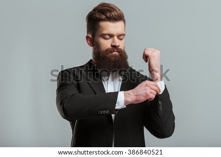 Handsome young bearded businessman in classic suit is adjusting his cufflink, on a gray background