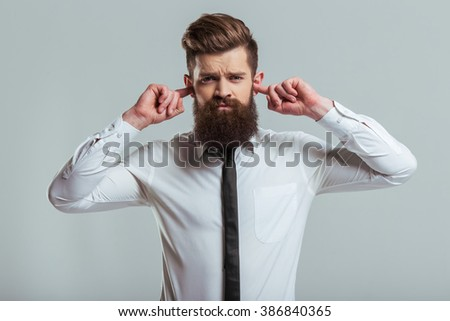 Handsome young bearded businessman in classic white shirt is covering his ears with fingers, on a gray background