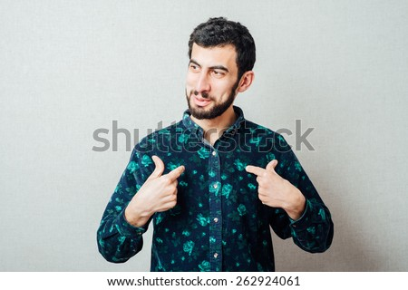 Handsome young bearded man gesturing to himself as if to say ; who me? - stock photo