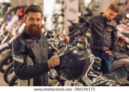 Handsome young bearded man in black leather jacket is holding a helmet, looking at camera and smiling while standing in a motorbike salon