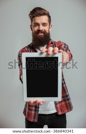 Handsome young bearded man in casual clothes is showing a tablet and smiling, on a gray background - stock photo