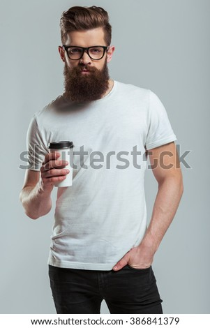 Handsome young bearded man in eyeglasses is holding a cup and looking at camera while standing against gray background - stock photo