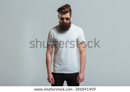Handsome young bearded man in sunglasses is looking at camera while standing against gray background - stock photo