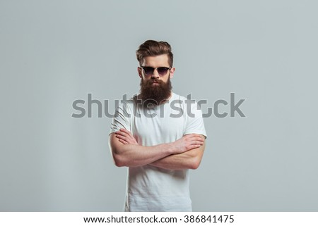 Handsome young bearded man in sunglasses is looking at camera while standing with crossed arms against gray background - stock photo