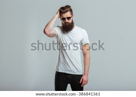 Handsome young bearded man in sunglasses is smoothing his hair and looking at camera while standing against gray background - stock photo