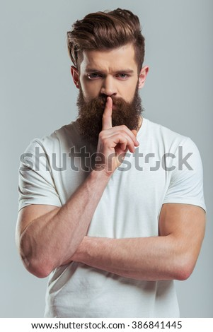 Handsome young bearded man is keeping finger on lips and looking at camera while standing against gray background - stock photo