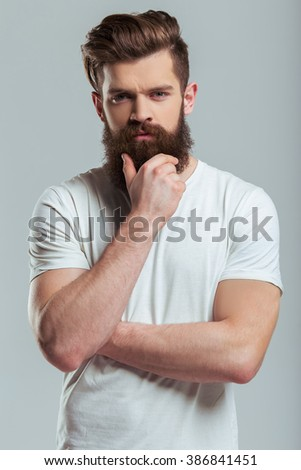 Handsome young bearded man is keeping hand on beard and looking at camera while standing against gray background - stock photo