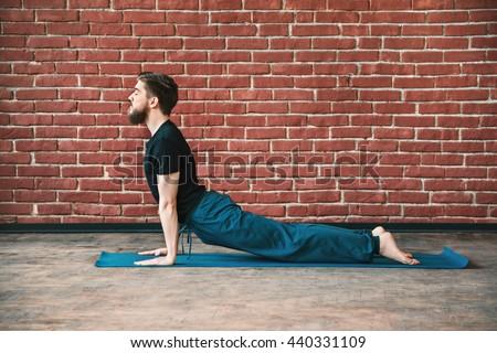 Handsome young bearded man with closed eyes wearing black T-shirt doing yoga position on blue matt at wall background, copy space, cobra asana, bhujangasana - stock photo