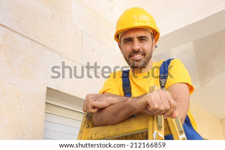 Handsome young bearded workman in a yellow hardhat and matching t-shirt standing on a wooden ladder