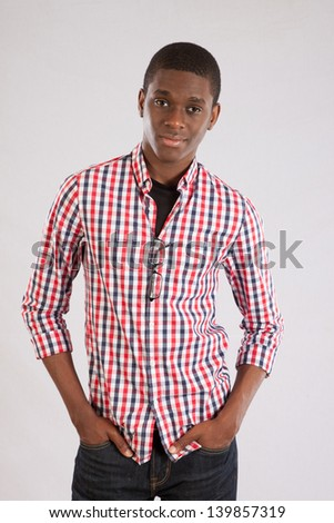 Handsome young black man, hands in his pockets, and looking at the camera with a thoughtful and friendly expression