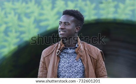 Handsome young black man smiles in front of an underpass with a painted surface