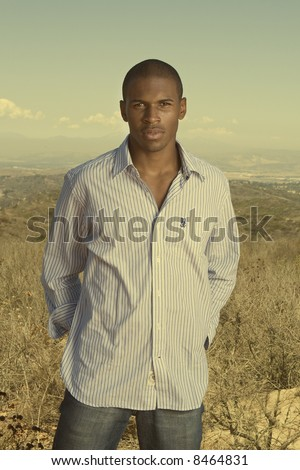 handsome young black man standing in a desert field - stock photo