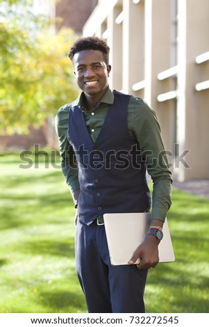 Handsome young black student man smiles standing on college campus with his computer