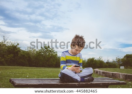 Handsome young blonde haired boy enjoying listening to music attentively, at the park - stock photo