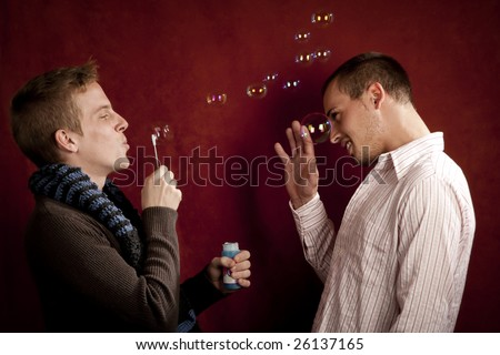 Handsome young blonde man blowing a bubbles at friends - stock photo