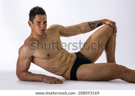 Handsome young bodybuilder laying down on the floor, showing ripped abs, muscular pecs, arms