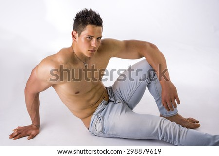 Handsome young bodybuilder laying down on the floor, showing ripped abs, muscular pecs, arms, shot from above - stock photo