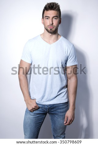 handsome young bodybuilder posing in casual clothes on grey background