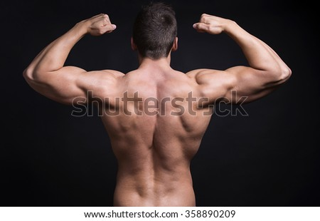 handsome young bodybuilder with toned body posing shirtless