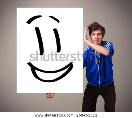 Handsome young boy holding smiley face drawing - stock photo