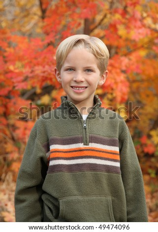 handsome young boy in sweater outdoors in autumn - stock photo