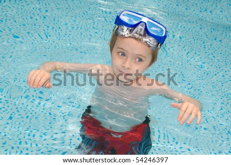 handsome young boy in Swimming Pool with googles - stock photo