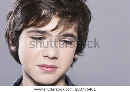 Handsome young boy looking down sad close up - stock photo
