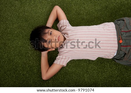 handsome young boy lying in the garden