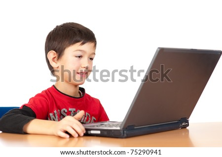 Handsome young boy plays with laptop isolated on white background