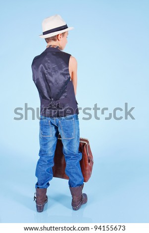 Handsome young boy wearing hat and with carpetbag - stock photo
