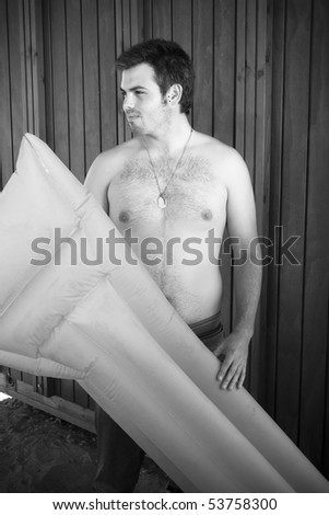 Handsome young boy with a beach mat - stock photo