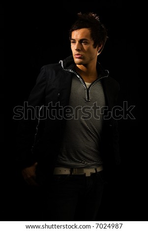 Handsome young brunette man wearing a striped shirt and dark jacket on black in shadow - stock photo