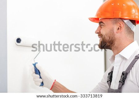 Handsome young builder is painting walls with a roller. He is standing and smiling - stock photo