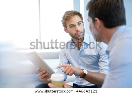 Handsome young business entrepreneur holding a digital tablet while talking about ideas with his mature corporate manager - stock photo