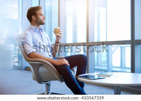 Handsome young business entrepreneur sitting in a bright modern office space, holding a cup of takeway coffee in his hand and daydreaming while looking out of large windows - stock photo
