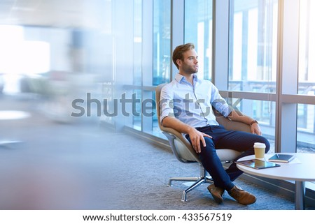 Handsome young business entrepreneur sitting in a modern office space, Looking out of large windows and thinking optimistically about the future - stock photo