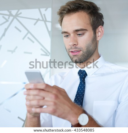 Handsome young business executive in a modern workplace looking at the screen of his mobile phone while typing a message - stock photo