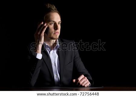 Handsome young business executive in dark suit sitting at office desk talking on mobile-phone, low-key image isolated on black background. - stock photo
