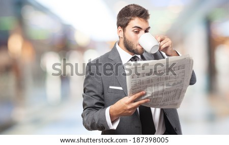 handsome young business man drinking and reading a newspaper - stock photo