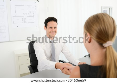 handsome young business man handshake with customer in office after signing agreement sales contract - stock photo